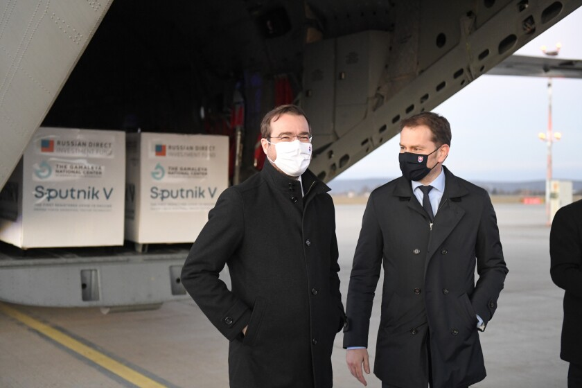 Slovak Prime Minister Igor Matovic, right, and Health Minister Marek Krajci at Kosice Airport, Slovakia, Monday March 1, 2021, as Russia's Sputnik V coronavirus vaccine arrives. Hard-hit Slovakia signed a deal to acquire 2 million dozes of Russia's Sputnik V coronavirus vaccine. The country's prime minister says Slovakia will get one million shots in next two months while another million will arrive in May and June. (Frantisek Ivan/TASR via AP)
