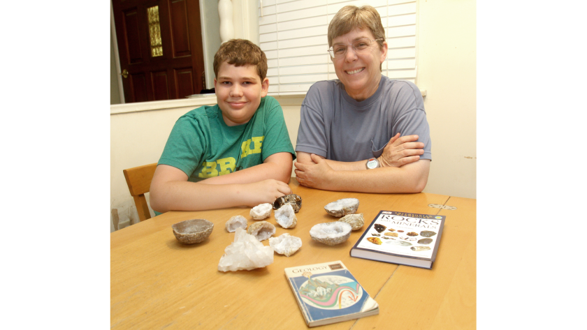 Kelly Duenckel, right, and her son Robert Duenckel, 13, at home showing some of the geodes he's collected along with some geology books.