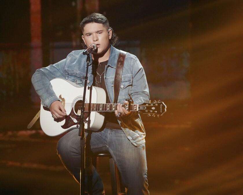 Caleb Kennedy holding a guitar