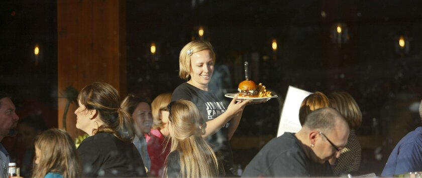 Server Crystal Dossman with a Blues Burger at Jimmy's Famous American Tavern.