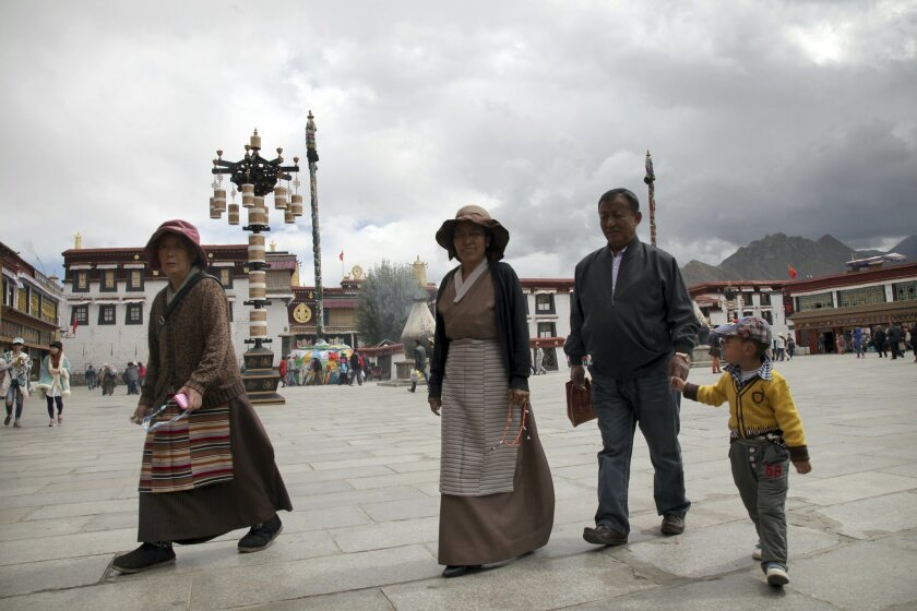 In this Friday, Sept. 18, 2015 photo, a Tibetan family walks across Jokhang Square in the center of Lhasa, capital of the Tibet Autonomous Region in China. Chinese officials have taken foreign journalists on a visit to the region, normally off-limits to them, weeks after Communist Party officials commemorated the 50th anniversary of the establishment of the Tibet Autonomous Region. (AP Photo/Aritz Parra)