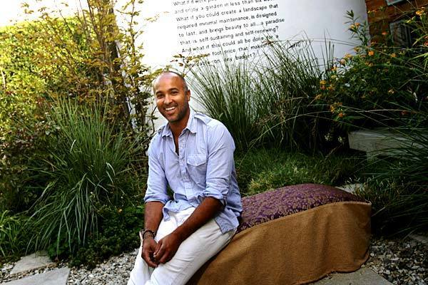 """Call it the modern urban meadow. After two decades of gardening, landscape designer Sean Knibb has come up with a formula for lush but water-wise, small-scale city gardens. Lawns are replaced with gravel, concrete pavers and low, mounding grasses nestled among ornamental varieties such as paspalum, shown here, beneath the writing on the wall behind Knibb. Traditionally separated cutting beds, vegetable patches and herb gardens are abolished. Succulents, shrubs, such as the yellow milkweed (far right), flowers and edibles all mingle in the same beds. """"Part of the aesthetic is to capture the look of where prairie meets forest,"""" Knibb says. """"The layering that happens in nature is the coolest thing."""" We recently toured three of Knibb's Los Angeles installations, each created from a palette of tough but showy plants and basic hardscape materials. Here, in the garden of his office and outdoor furniture showroom, Knibb sits on a slip-covered bale of hay that serves as a bench. (Keep clicking to see what he's done and close-up looks at some of the flowers.)"""