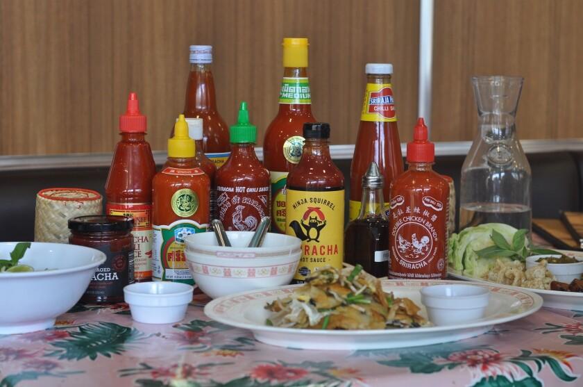 Bottles of Sriracha for sampling line the table at Pok Pok LA, Andy Ricker's Thai restaurant in Chinatown.