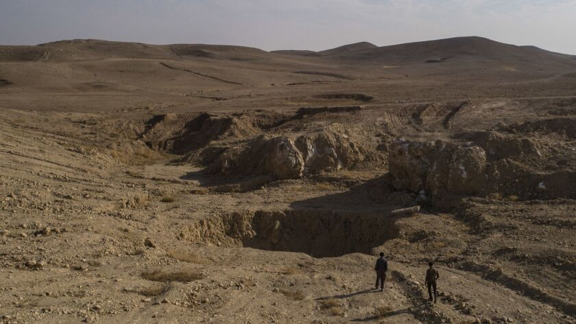 In this Nov. 11, 2017 photo, two Iraqi men walk near a sinkhole known as Khasfa, that is believed to