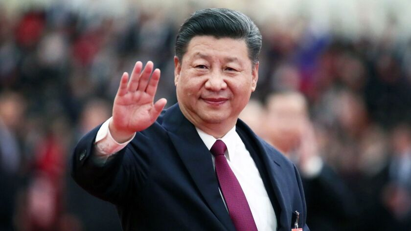 Chinese President Xi Jinping waves to elected deputies after the closing session of the annual National People's Congress at the Great Hall of the People in Beijing.