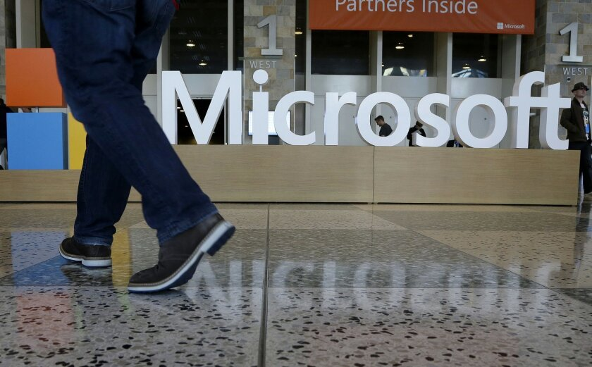FILE - In this April 28, 2015 file photo, a man walks past a Microsoft sign set up for the Microsoft BUILD conference at Moscone Center in San Francisco. Starting next year, Microsoft will cut the free space it offers through its OneDrive service to 5 gigabytes, down from 15 gigabytes now. Microsof