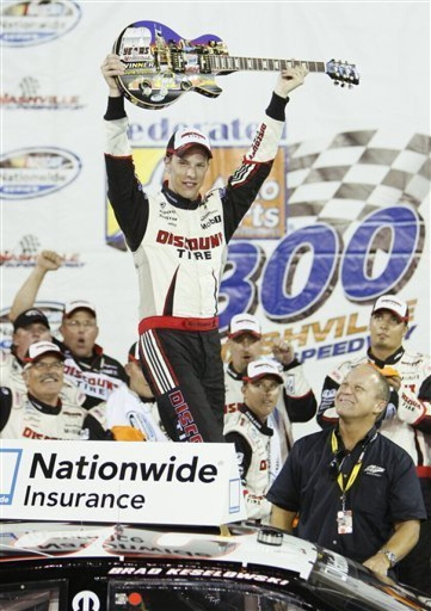 Driver Brad Keselowski raises the custom Gibson guitar trophy after winning the NASCAR Nationwide Series Federated Auto Parts 300 auto race in Gladeville, Tenn., Saturday, June 5, 2010.(AP Photo/Wade Payne)