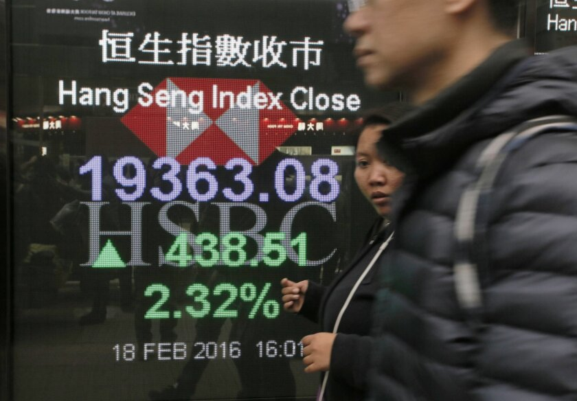 People walk past a bank's electronic board showing the Hong Kong share index at Hong Kong Stock Exchange Thursday, Feb. 18, 2016. Asian stocks mostly posted strong gains on Thursday as a rebound in the price of oil and solid U.S. manufacturing data boosted European markets and Wall Street. Hong Kon