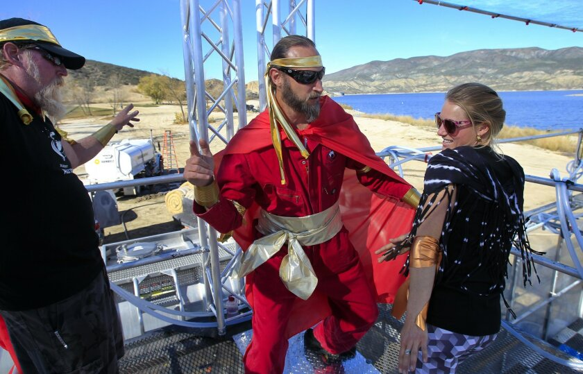 David Bronner, president of Dr. Bronner's Magic Soaps, center, along with Mia Hardwick and Dan Anderson, left, dance on the catwalk above Dr. Bronner's All-One Magic Foam Experience at the end of Spartan Race 2015, at the Vail Lake Resort in Temecula.