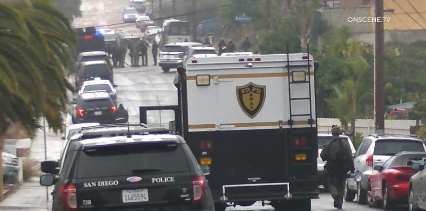 A man suspected of holding his wife hostage surrendered to police after a SWAT standoff early Monday.