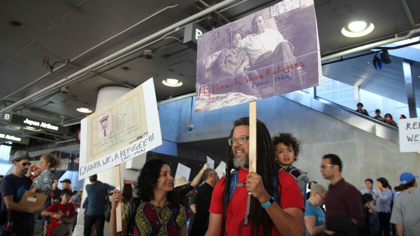 Painter Carolyn Castaño and writer Gary Dauphin protest at LAX with their son, Toussaint.