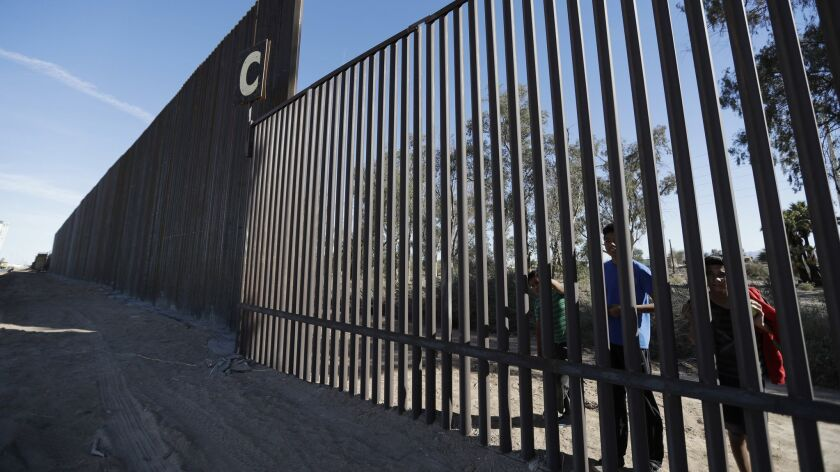 FILE - In this March 5, 2018, file photo, boys look through an older section of the border structure