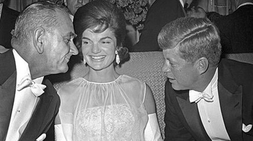 Vice President Lyndon B. Johnson chats with President Kennedy and First Lady Jacqueline Kennedy at the inaugural ball in 1961. Kennedy's gowns were inspired by French haute couture but made in America.
