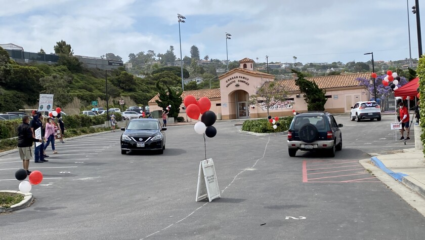 La Jolla High staff and faculty with signs and balloons cheer for Class of 2020 seniors, accompanied by music from a DJ.