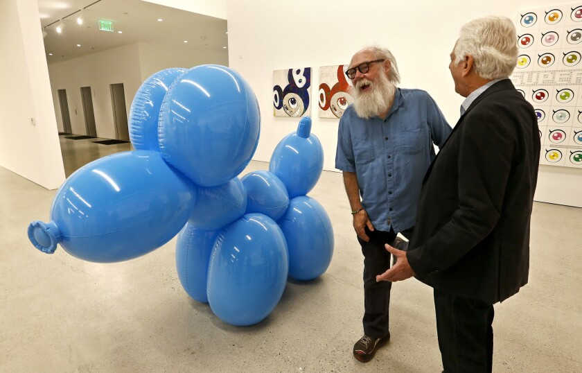 "Artist Paul McCarthy, left, shares a laugh with Maurice Marciano, founder of the Marciano Art Foundation, next to McCarthy's work, ""White Snow, Balloon Dog."""