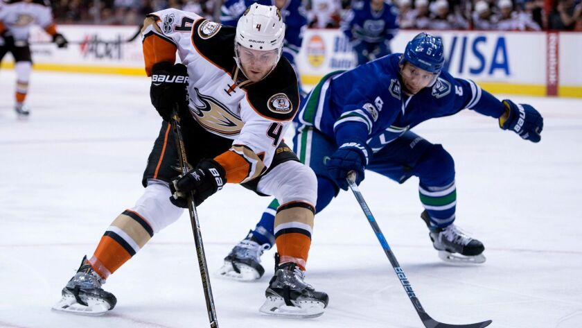 Ducks defenseman Cam Fowler vies for control of the puck with Vancouver's Luca Sbisa on March 28.