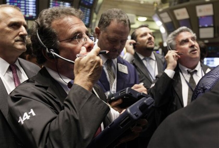 In this Sept. 30, 2010 photo, traders gather at a post on the floor of the New York Stock Exchange, in New York. U.S. stock futures are rising Tuesday, Oct. 5, 2010, following world markets higher after the central bank of Japan moved to weaken the yen.(AP Photo/Richard Drew)
