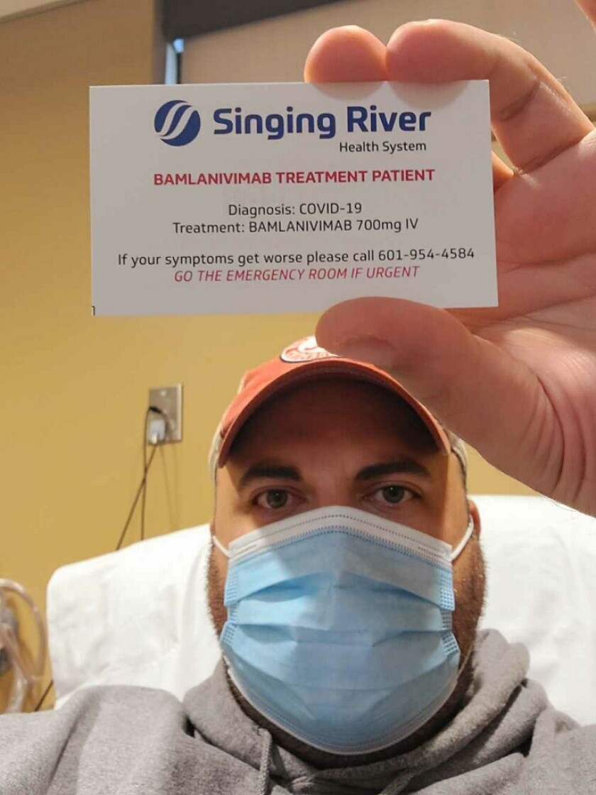 COVID-19 patient Gary Herritz of Pascagoula, Miss., holds a card identifying him as a monoclonal antibody therapy recipient.