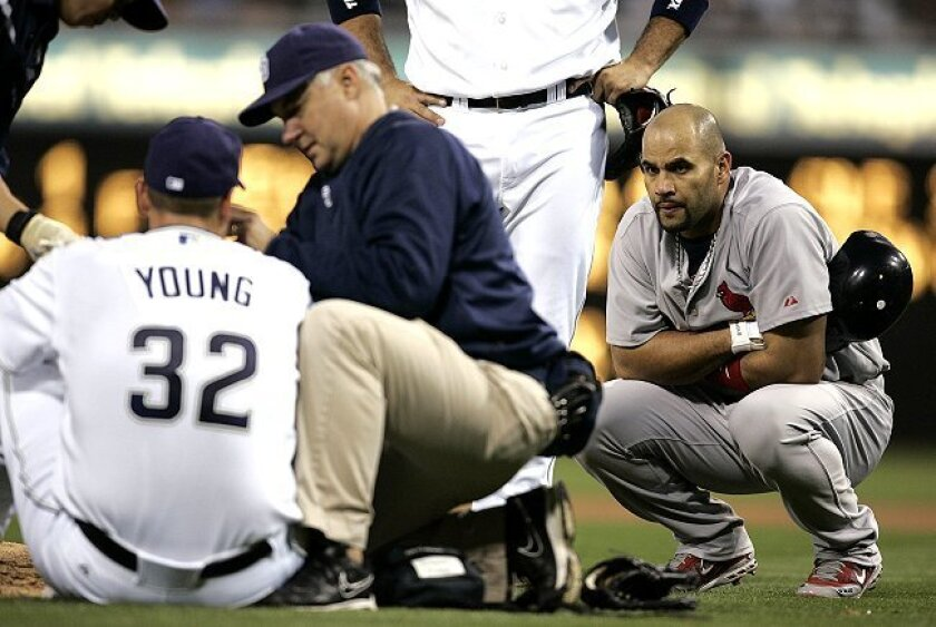 Albert Pujols (right) watched as Padres pitcher Chris Young was attended to by trainer Todd Hutcheson after a Pujols line drive hit Young in the face on May 21, 2008.