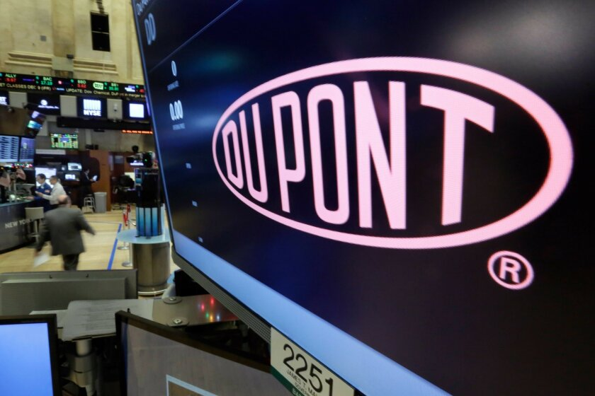 FILE - In this Dec. 9, 2015 file photo, the company name of Dupont appears above its trading post on the floor of the New York Stock Exchange. Shareholders for agriculture and chemicals companies DuPont and Dow Chemical have approved their merger, as well as a subsequent plan that will break up the