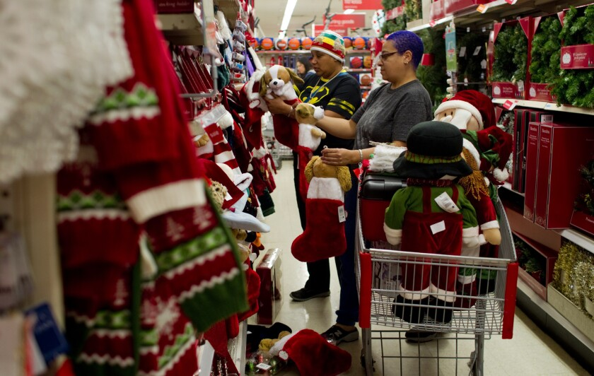 Katie Rainey of Los Angeles, left, and Michelle Roache of Burbank fill their shopping cart with Christmas decorations with a pet theme at Kmart in Burbank in 2013. Early data says Super Saturday surpassed Black Friday in sales this year.