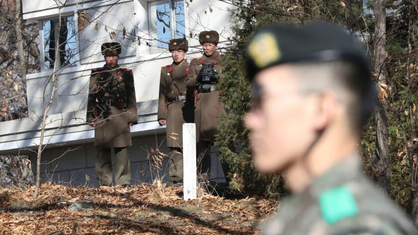 North Korean soldiers and a South Korean soldier, right, in the Demilitarized Zone on Nov. 27.