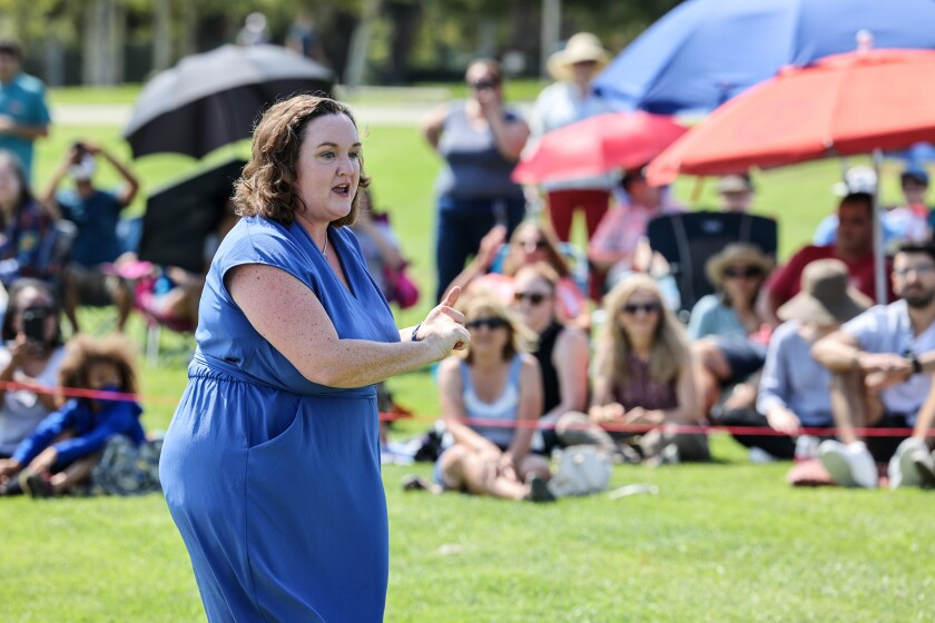 Katie Porter, outdoors on a stretch of grass, speaks to people sitting on the ground and beneath umbrellas.