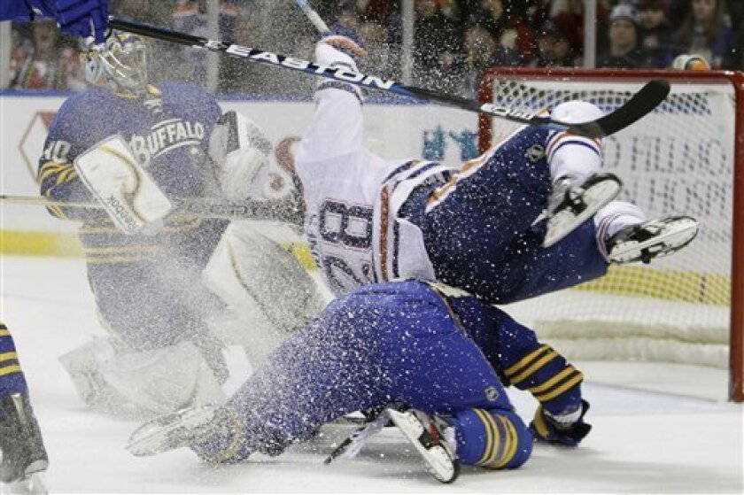Buffalo Sabres' T. J. Brennan, bottom, collides with Edmonton Oilers' Ryan Jones, top, during the second period of an NHL hockey game in Buffalo, N.Y., Tuesday, Jan. 3, 2012. (AP Photo/David Duprey)