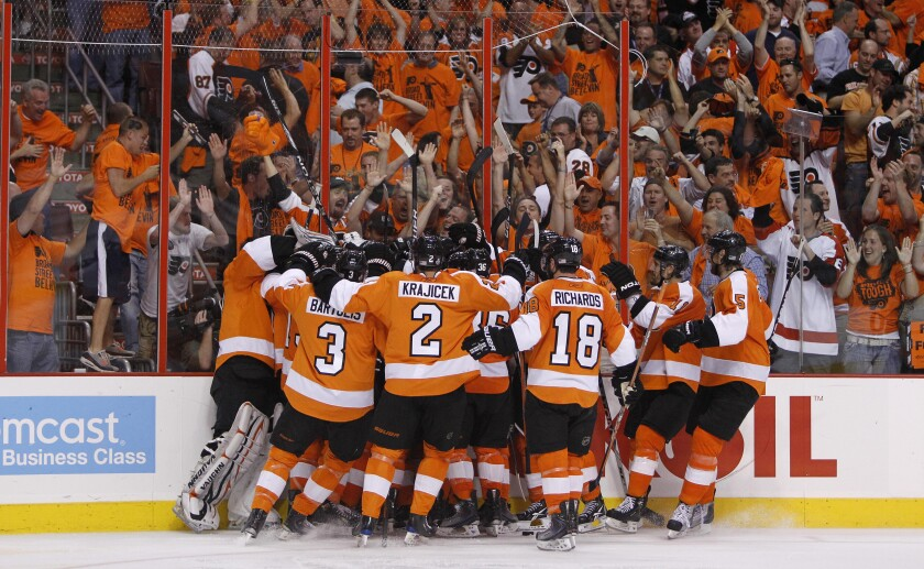 FILE - Philadelphia Flyers players and fans celebrate after the Flyers beat the Chicago Blackhawks 4-3 in overtime on a goal by Claude Giroux in Game 3 of the NHL Stanley Cup hockey finals in Philadelphia, in this Wednesday, June 2, 2010, file photo. The Flyers once routinely packed the arena and the orange-and-black faithful could make Philly the best hockey city in the league. The Flyers have now dropped behind the other pro teams in the city when it comes to buzz and fan interest. (AP Photo/Matt Slocum, File)