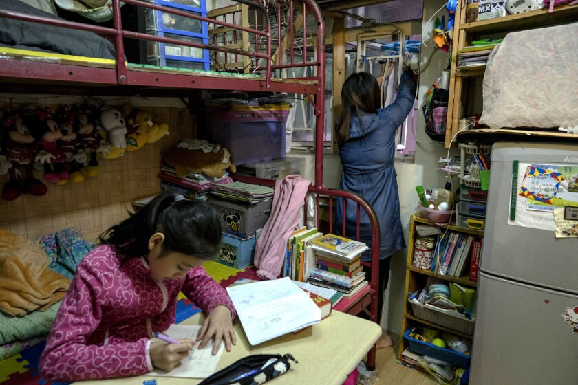 May Han does household chores as her daughter, aged 11, studies in their one room flat in Mong Kok,