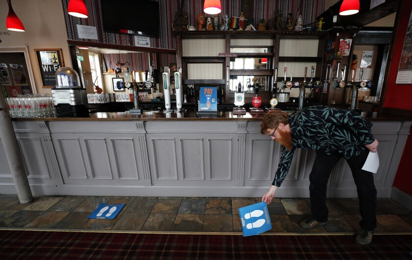 Owner Are Kjetil Kolltveit from Norway places markers for social distancing on the front of the bar at the Chandos Arms pub in London, Wednesday, July 1, 2020. Asking people in English pubs to keep their distance is going to be tough after they've had a few of their favorite tipples. Pub managers will have to be resourceful come Saturday, July 4, 2020, when they and other parts of the hospitality industry in England open their doors to customers for the first time since March 20, provided they meet COVID safety requirements. (AP Photo/Frank Augstein)