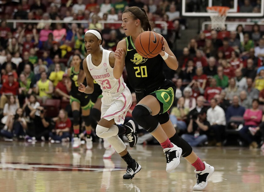 Oregon's Sabrina Ionescu drives the ball up court past Stanford's Kiana Williams. Ionescu became the first NCAA player to reach 2,000 points, 1,000 assists and 1,000 rebounds hours after speaking at Kobe Bryant's memorial.