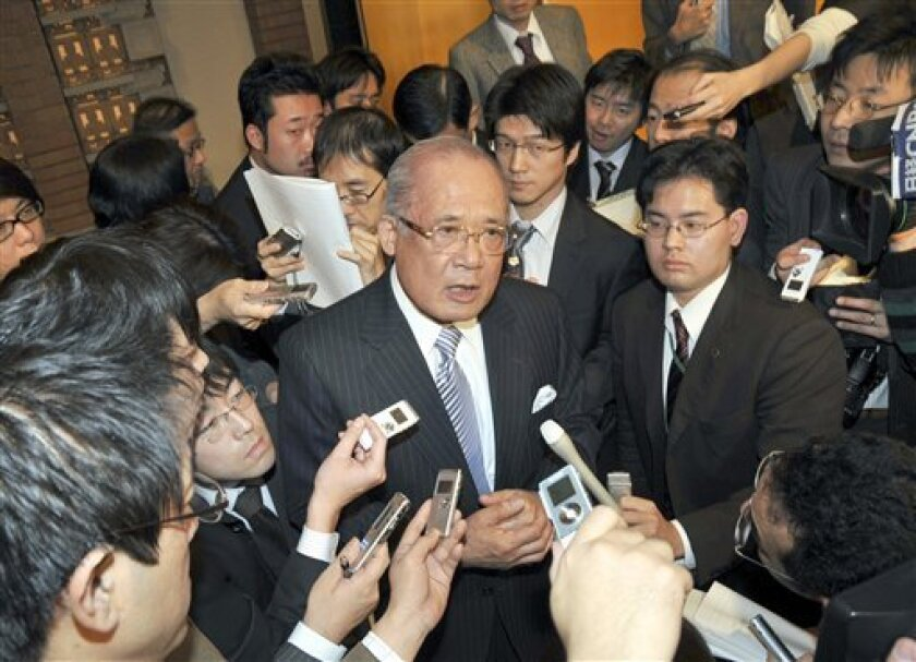 Nippon Oil Corp. President Shinji Nishio, center, is surrounded by reporters after a joint press conference with Nippon Mining Holdings Inc. President Mitsunori Takahagi at a hotel in Tokyo, Thursday, Dec. 4, 2008. Japan's top oil distributor, Nippon Oil Corp., is merging with the smaller rival in a bid to weather sluggish demand and better respond to ecological concerns, both companies said Thursday. (AP Photo/Katsumi Kasahara)