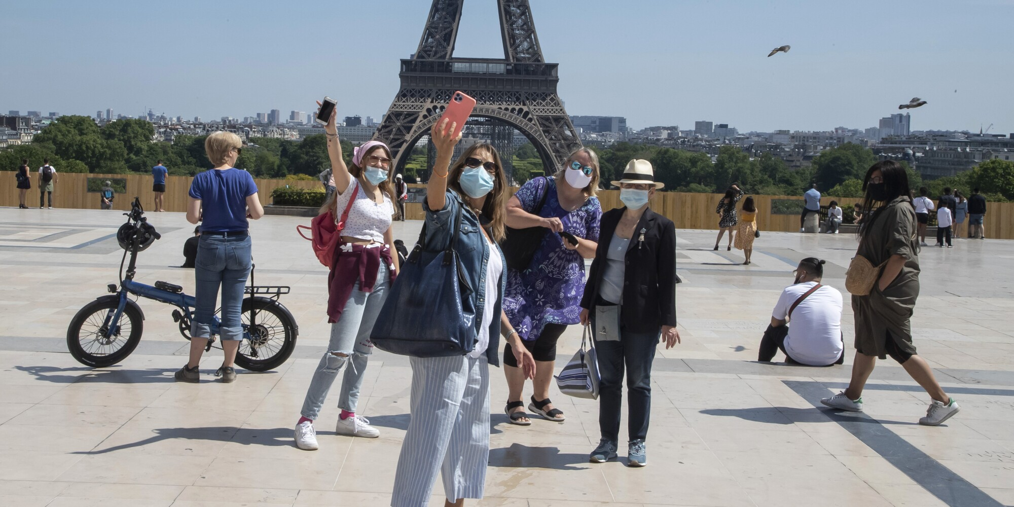 Visitors take a selfie at the Eiffel Tower on Sunday.
