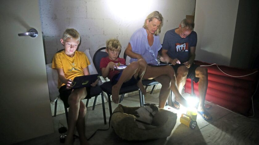 The Blinckman family use their personal devices while sheltering in a stairwell utility closet as Hurricane Irma goes over Key West, Fla., Sept. 10, 2017.