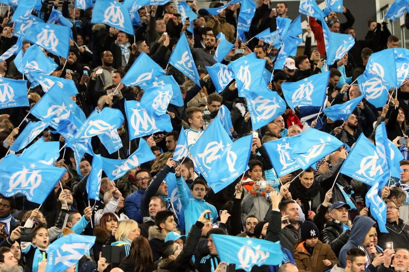 Marseille supporters wave flags during the League One soccer match between Marseille and Paris Saint-Germain, at the Velodrome Stadium, in Marseille, southern France, Sunday, Feb. 7, 2016. (AP Photo/Claude Paris)