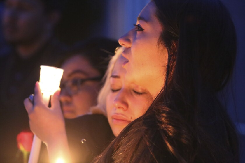 FILE - In this March 5, 2020, file photo, Isis and Alexis Valenzuela, daughters of Antonio Valenzuela, hug each other during a candlelight vigil in Las Cruces, N.M. Antonio Valenzuela was killed by a Las Cruces police officer in February. As national Black Lives Matter demonstrations grow, Latino activists are joining the multiracial protests while trying to draw attention to their deadly police encounters, some of which go back decades. (Bethany Freudenthal/The Las Cruces Sun News via AP, File)