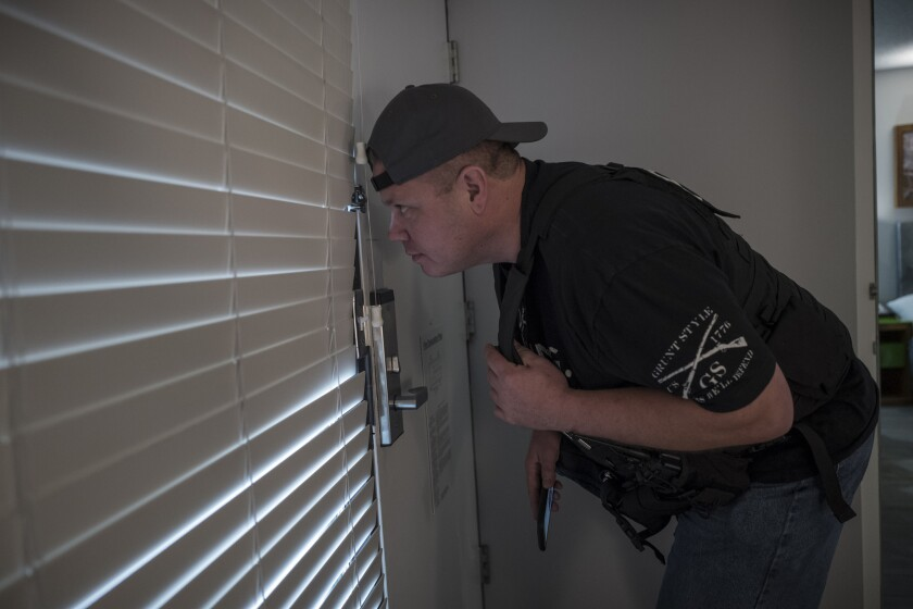 At a Santa Clara hotel for a sting operation targeting prostitution and human trafficking, California Parole Officer J. Routt waits for suspects to arrive.