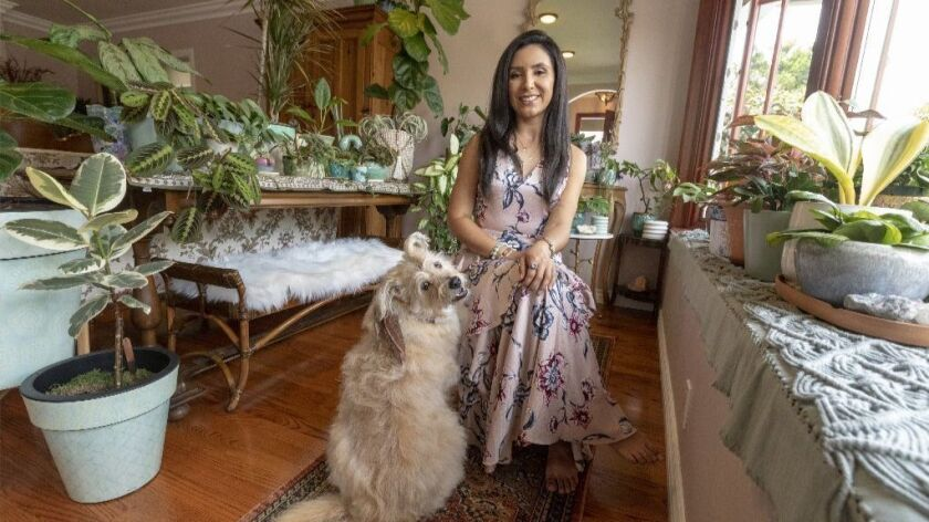 Darlene Zavala, in her living room with her house plants and dog Lialah.