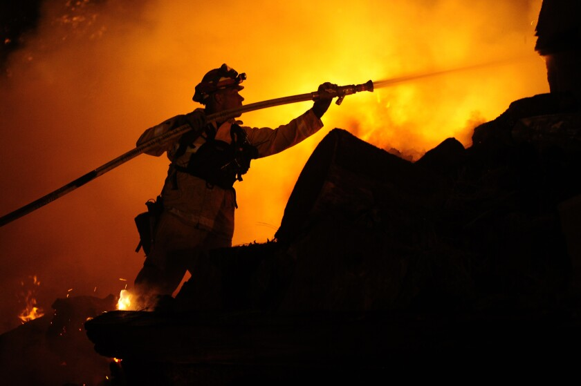 A nighttime photo of a firefighter silhouetted against flames.