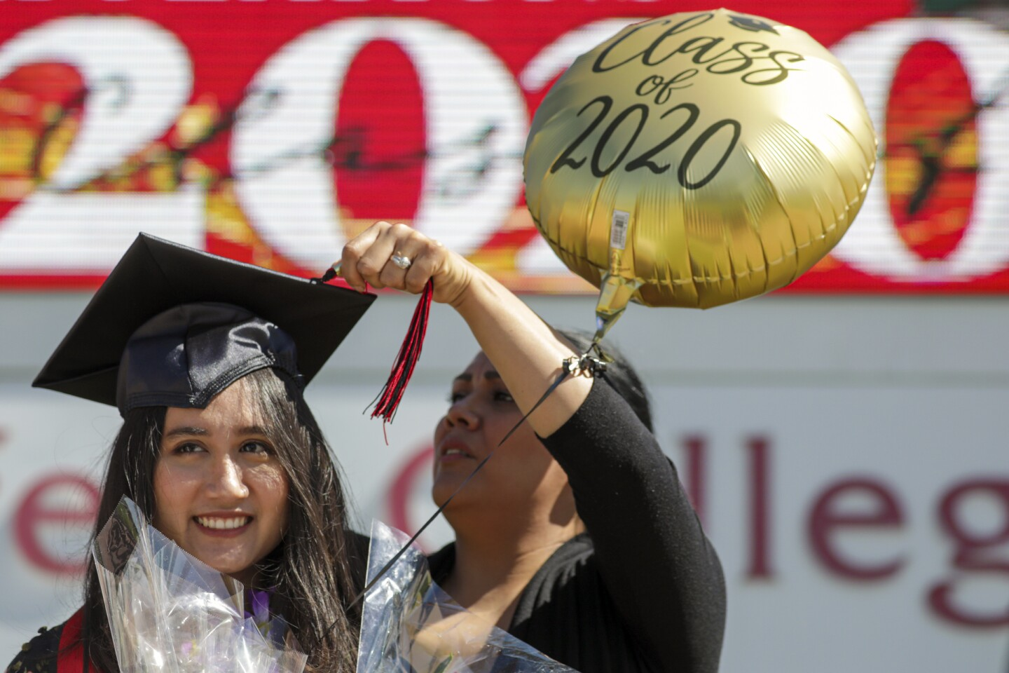 "RANCHO CUCAMONGA, CA - MAY 20: Melissa Gomes, right, fixes the tassel as new graduate Sarah Anggraini gets ready for a photo at the marquee of Chaffey Colleges that held a drive through graduation on Wednesday, May 20, 2020 in Rancho Cucamonga, CA. Chaffey College handed out 600 ""Grad Bags"" at the Rancho Cucamonga campus, and around 170 each at the Chino and Fontana campuses. Chaffey will award about 6,400 degrees and certificates to the Class of 2020, the most awarded in the college's history. (Irfan Khan / Los Angeles Times)"