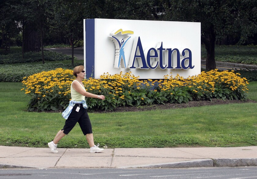 A woman strides past the Hartford, Conn., headquarters of Aetna, Inc.