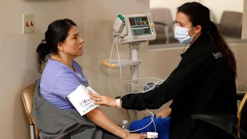 La enfermera Marenna Bielman (d) saca sangre a Angelica Lara, mientras es tratada por síntomas parecidos a la gripe en el Hospital St. Joseph en Orange.