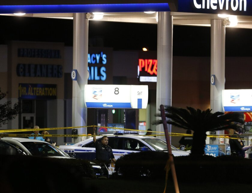 Officials investigate the gas station where a sheriff's deputy was fatally shot while filling up his patrol car Friday night outside Houston.