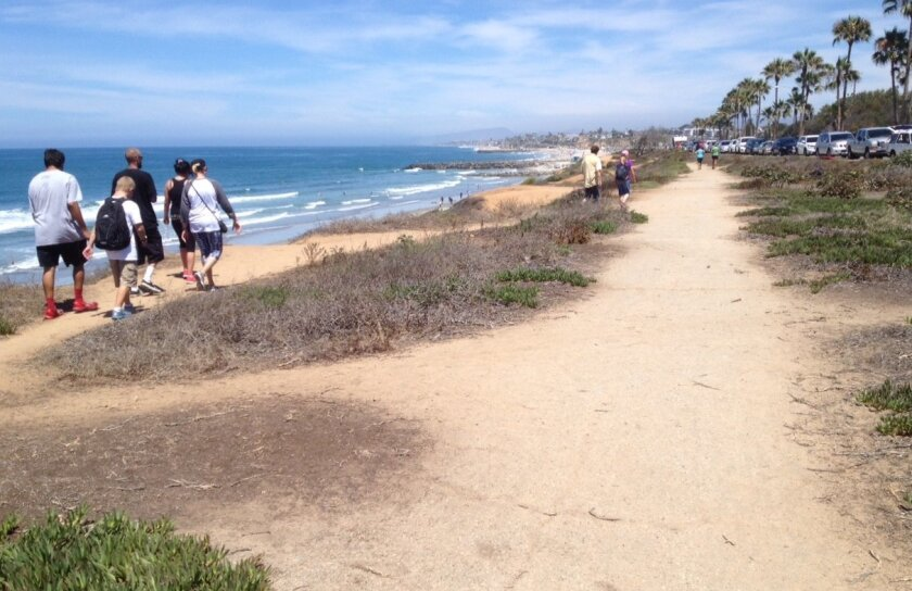 Visitors walk along the edge of the ocean bluff across Carlsbad Boulevard from the Encina power plant, part of the Terramar Area Coastal Improvement Project.
