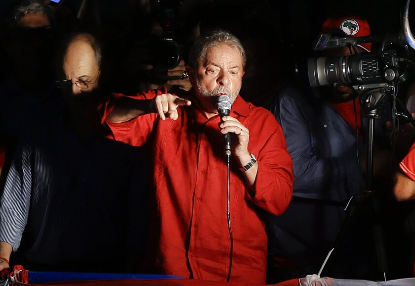 Brazil's former President Luiz Inacio Lula da Silva speaks during a rally in support of him and Brazil's President Dilma Rousseff, in Sao Paulo, Brazil, Friday, March 18, 2016. Supporters of Silva, who was one of the world's most famous leaders as president from 2003 to 2010, gathered for rallies in a handful of cities across Brazil, particularly in the industrial south, where the former factory worker has his base. Silva has been tied to a sprawling corruption investigation involving the Brazil oil giant Petrobras.(AP Photo/Andre Penner)