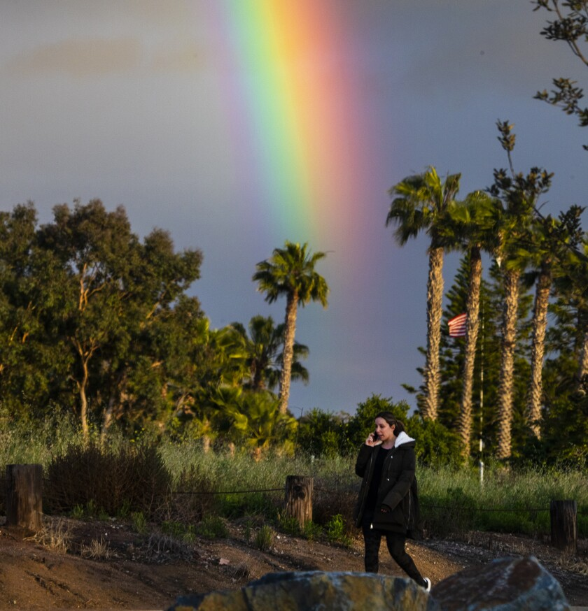 COSTA MESA, CA -- FRIDAY, APRIL 10, 2020: A rainbow appears behind a woman walking through Fairview Park in Costa Mesa on Good Friday April 10, 2020. Heavy rain is expected in Southern California on Friday as a low pressure system brings more moisture. About 1-2 inches of rain is expected in Los Angeles and Orange counties with temperatures reaching a high of 68 degrees. (Allen J. Schaben / Los Angeles Times)