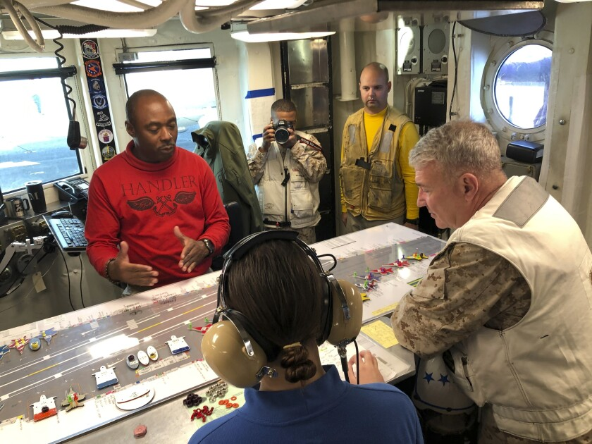 Marine Gen. Frank McKenzie, top U.S. commander for the Middle East, right, listens as Lt. Maguel Brooks, the USS Harry S. Truman's handler, left, explains the movement of aircraft on the aircraft carrier's flight deck, on board the USS Harry S. Truman aircraft carrier in the North Arabian Sea, Saturday, Feb. 1, 2020. Nearly a month after Iran launched a rare direct military attack against United States forces in Iraq, an uneasy quiet has settled across the region. Watching fighter jets roar off the flight deck of the USS Harry S. Truman, the top U.S. commander for the Middle East believes he is surrounded by one of the reasons that Iran has dialed back it's combat stance, at least for now. He says the presence of an aircraft carrier make a potential adversary think twice about war. But he and other commanders on the ship agree that deterrence is hard to measure. (AP Photo/Lolita Baldor)