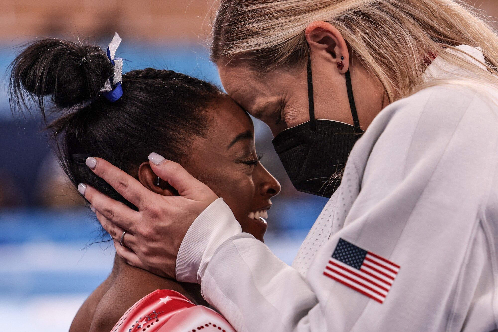 Cecile Landi presses her forehead to that of Simone Biles.