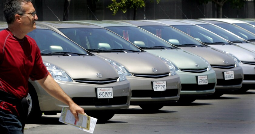 A traveler walks by a line of Toyota cars parked at the Hertz's rental lot near Los Angeles International Airport. Rates for car rentals have dropped thanks to increased competition.